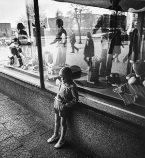 Child near the shop window. Vilnius